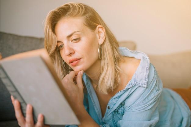 Close-up van blonde jonge vrouw met hand op kin die het boek leest