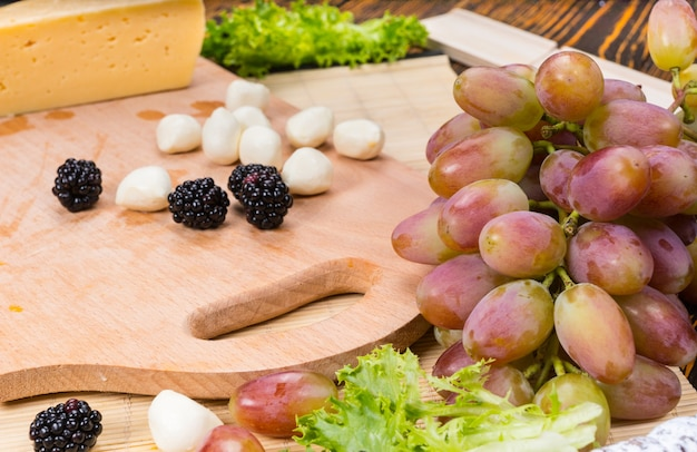 Close up van bocconcini en bramen gegarneerd met rode druiven geserveerd op een houten kaasplankje voorgerecht