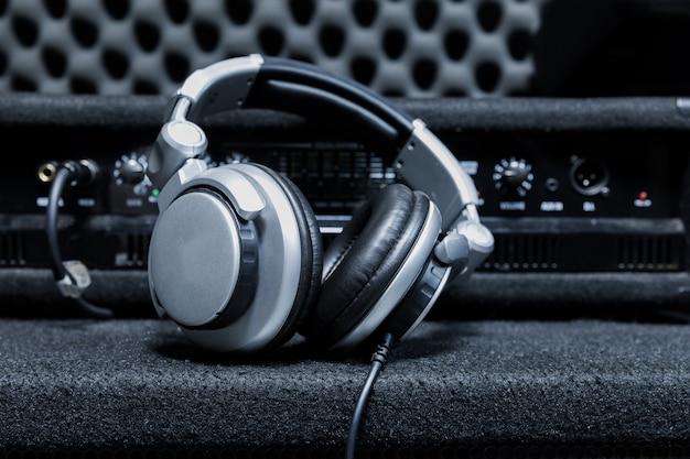 Close-up van boetiek opnamestudio bedieningsbureau, dj-hoofdtelefoon voor professionele disc, apparatuur voor geluidsopnamestudio, mixer en dj-hoofdtelefoon
