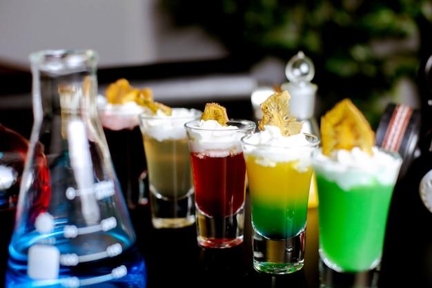 Close up van borrelglaasjes met cocktails gegarneerd met slagroom en gedroogde vruchten