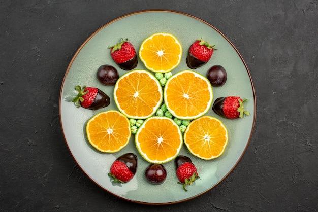 Close-up van bovenaanzicht fruit en chocolade gehakte sinaasappel met chocolade bedekte aardbeien en groene snoepjes