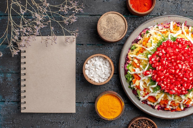 Close-up van bovenaanzicht kerstschotel met granaatappels een smakelijk kerstschotel met granaatappelpitten naast de witte notitieboekjeboomtakken en vijf kommen met kleurrijke kruiden op tafel