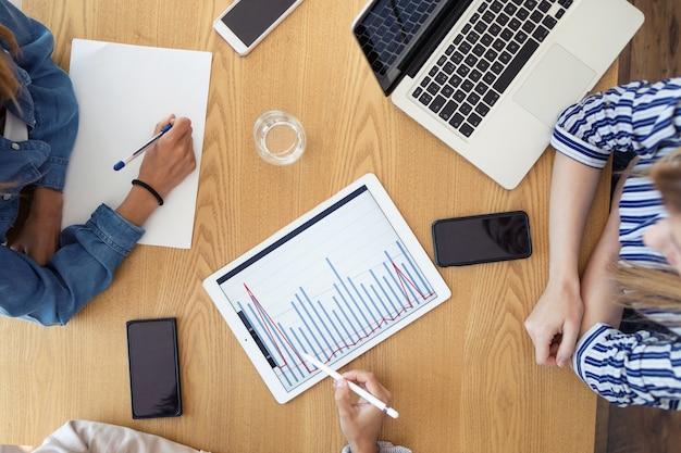 Close-up van bovenaanzicht van drie zakenvrouwen die digitale tablet gebruiken tijdens het werken met collega's aan een nieuw project op kantoor.