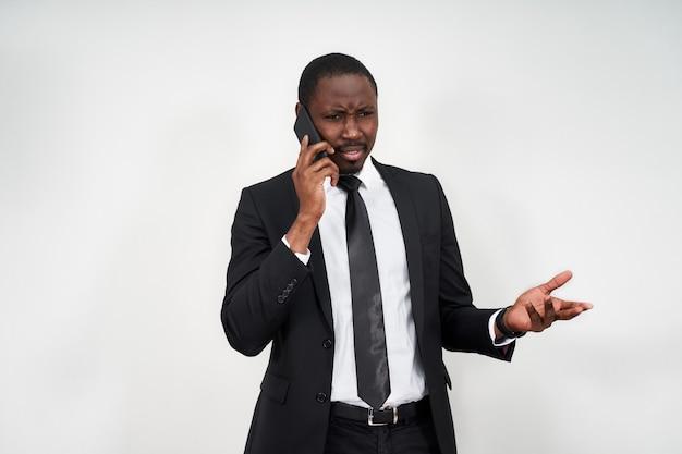 Close-up van boze jonge afrikaanse man schreeuwen tijdens het praten op smartphone