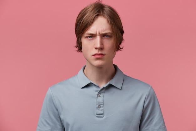 Close-up van boze woedende ontevreden netjes gekamde jonge kerel, gefronste wenkbrauwen, agressieve ogen, gekleed in casual poloshirt, geïsoleerd op roze achtergrond