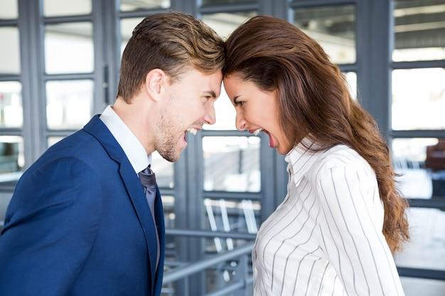 Close-up van boze zakenman en onderneemster die zich head to head bevinden