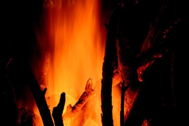 Close-up van brandende logboeken in de open haard op zwarte achtergrond