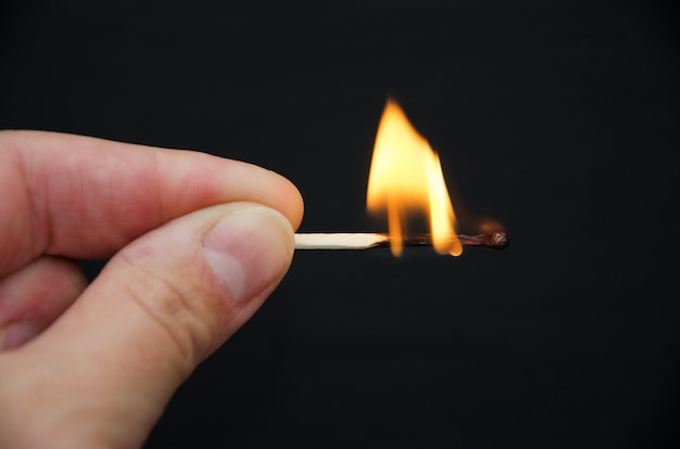 Close-up van brandende lucifer in de hand op zwart.