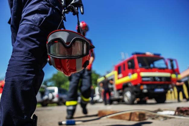 Close-up van brandweerman die zijn helm houdt en naar brandweerwagen loopt.