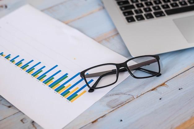 Close up van bril, laptop en grafiek met stadistieken op een blauwe houten tafel - zakenman of vrouw levensstijl
