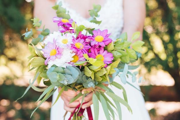 Close-up van bruid die kleurrijk bloemboeket houdt