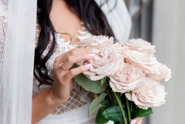 Close-up van bruid die roze rozen vasthoudt, zonder gezicht