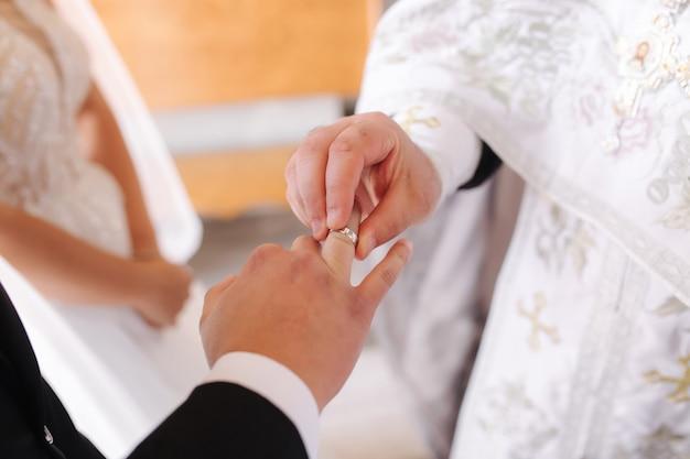 Close-up van bruidegom en bruid zetten hun ringen op vinger in de kerk.
