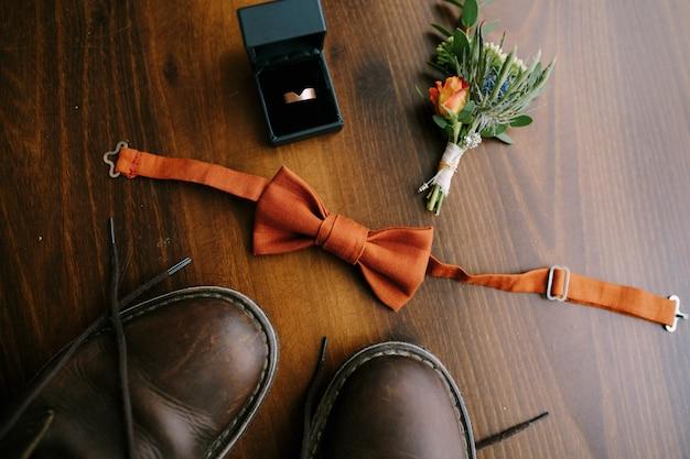 Close-up van bruidegoms vlinderdas met corsages heren verlovingsring in een doos en herenlaarzen op bruin