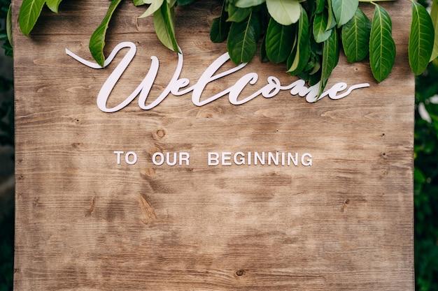 Close-up van bruin bord met witte letters en groene bladeren van bovenaf inscriptie welkom bij onze
