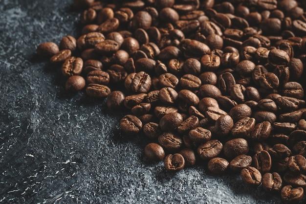 Close-up van bruine koffiezaden op donker