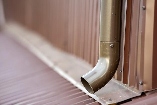 Close-up van bruine nieuwe het systeempijp van het gootmetaal op muur. afvoerbeveiliging, professioneel werk.