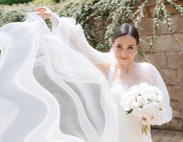 Close up van brunette bruid staat op straat met een boeket in haar handen en houdt een witte sluier vast