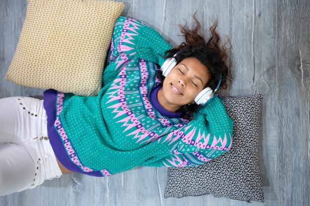 Close up van brunette meisje genieten van haar vrije tijd luisteren naar muziek liggend op de vloer van haar huis. ruimte voor tekst.