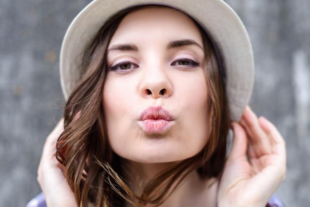 Close up van brunette vrouw kus verzenden in hoed