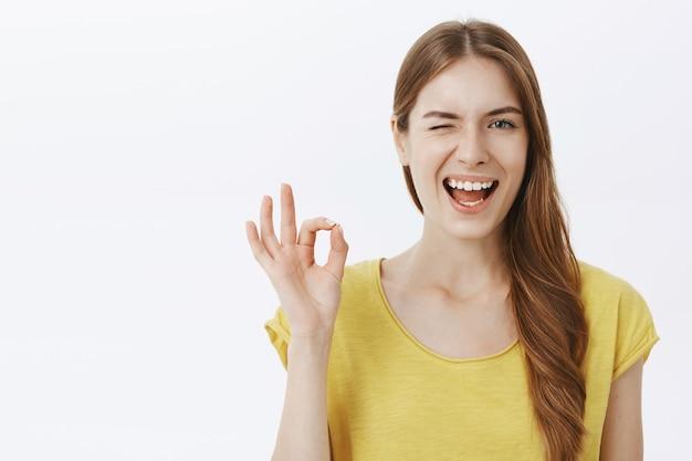 Close-up van brutaal aantrekkelijk meisje glimlachend en knipogen, ok gebaar ter goedkeuring tonen