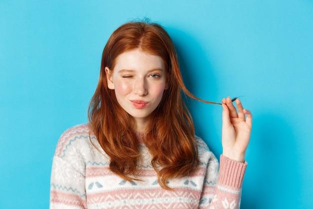 Close-up van brutaal roodharig meisje dat met haarstreng speelt, knipoogt en glimlacht naar de camera, staande over blauwe achtergrond
