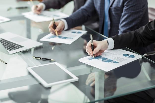 Close-up van business team dat een nieuw financieel plan van het bedrijf bespreekt op de werkplek op kantoor