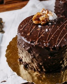 Close up van cake bedekt met chocolade en walnoten op de tafel