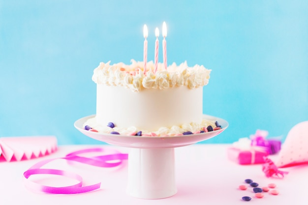 Close-up van cake met brandende kaarsen op roze achtergrond