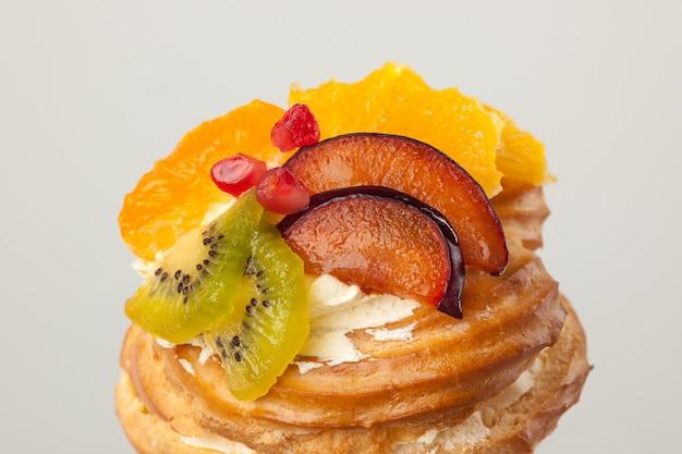 Close-up van cake met vers fruit op grijs.
