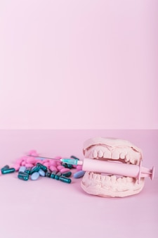 Close-up van capsules en pillen naast tandenvorm met spuit