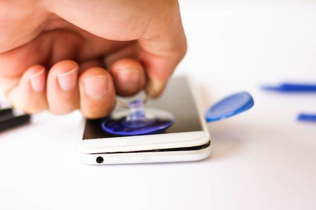 Close-up van cellphone repareren, open de klep van de telefoon
