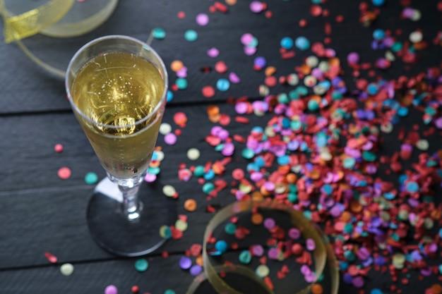 Close-up van champagnebellen in glas en feestconfettien