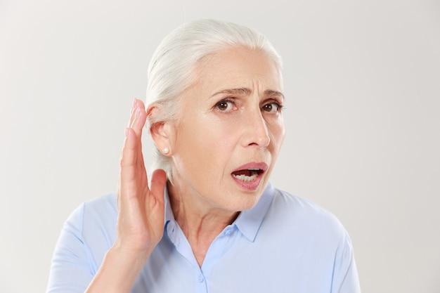 Close-up van charmante bejaarde vrouw, die hand bij haar oor houdt en worstelt om iets te horen