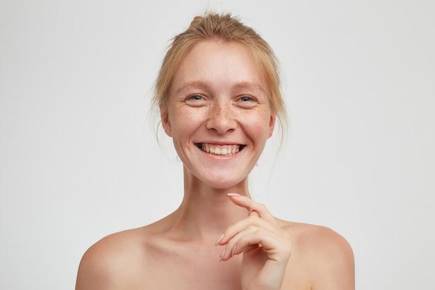 Close-up van charmante jonge roodharige vrolijke dame met knot kapsel toont haar tanden terwijl ze breed lacht en hand opstekend naar haar gezicht, geïsoleerd over witte muur