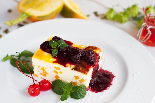 Close-up van cheesecake met kersen en jam op witte plaat.