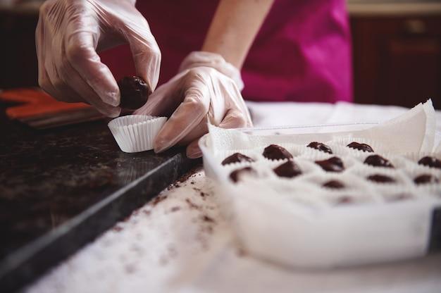 Close-up van chef-banketbakker handen chocoladesuikergoed aanbrengend een papieren wikkel en chocolade truffels verpakken in vak. .