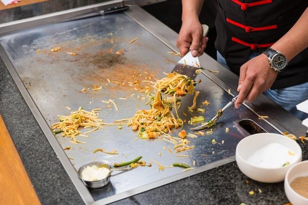 Close-up van chef-kok die aziatische noedels bereidt op een metalen flat top grill