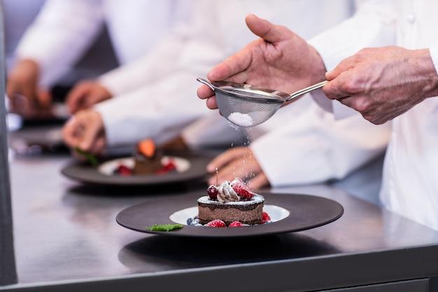 Close-up van chef-kok die een dessertplaat beëindigt