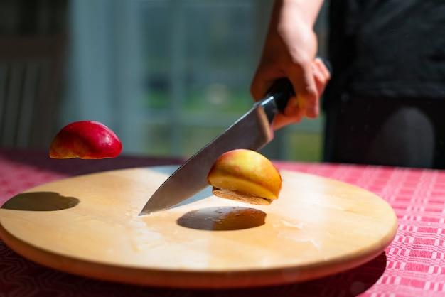 Close-up van chef-kok hand appel doormidden hakken met keukenmes op tafel.