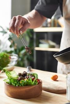 Close-up van chef-kok kookschotel met gebakken vlees aan de tafel in de keuken