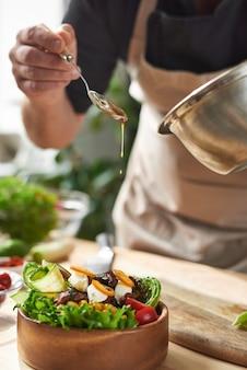 Close-up van chef-kok sojasaus in schotel met vlees en groenten aan de lijst toe te voegen