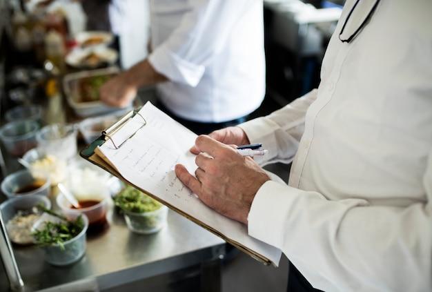 Close-up van chef-kokhand die menulijst controleert