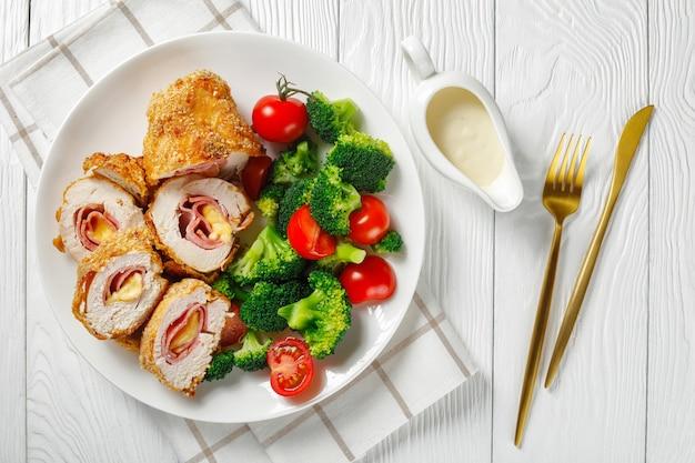 Close-up van chicken cordon bleu geserveerd op een witte plaat