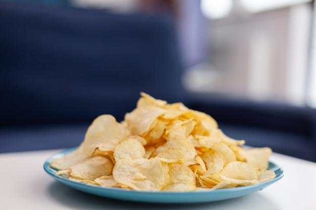 Close up van chips snack zittend op de salontafel. moderne woonkamer met niemand binnen met blauwe meubels en muren, mooi ingericht. vrij eenvoudige inrichting van appartement. elegante retro decoratie, gezellig.