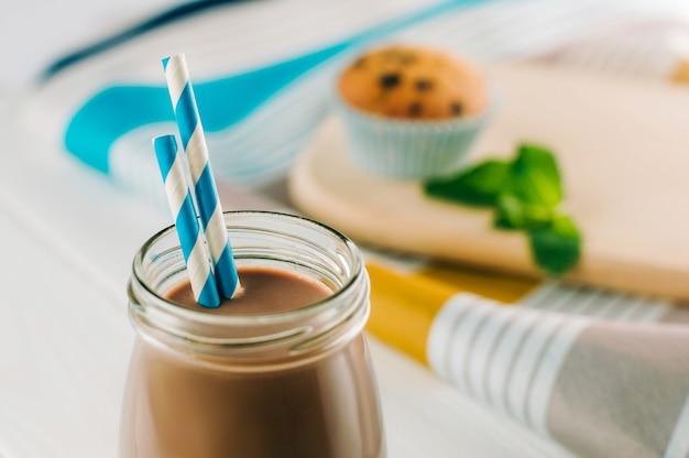 Close-up van chocolademelk in glazen fles met blauw gestreepte rietjes