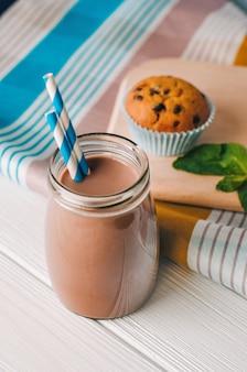 Close-up van chocolademelk in glazen fles met cake