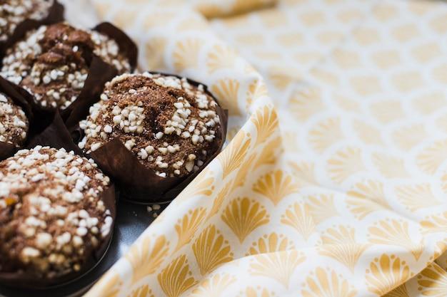 Close-up van chocolademuffins in bruin papier over het tafelkleed