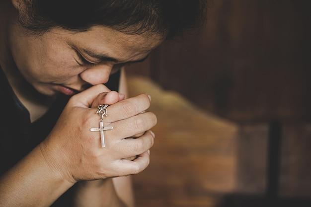 Close-up van christelijke hogere vrouwenhanden die gekruisigd kruis houden terwijl het bidden van god.