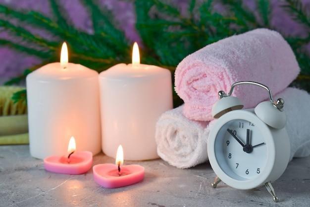 Close-up van christmas spa-samenstelling, kaarsen, wekker en handdoeken